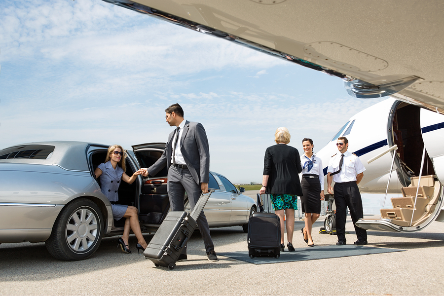 Business partners about to board private jet while airhostess an