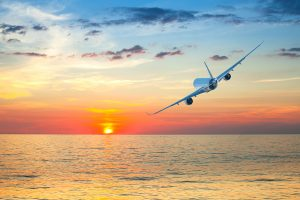 Jumbo jet airplane flying above tropical sea at beautiful sunset